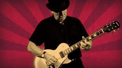 Stewart playing guitar in Steam Punk video